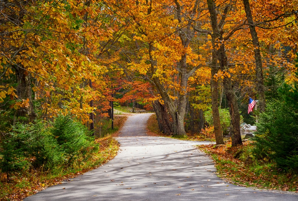 Winding country road in autumn with American flag on road side